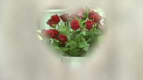 En bukett av röda rosor till och med hjärtan