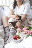 En bukett av rosa rosor, i händerna av en bok för flicka` s, bär av jordgubbar och doftande kaffeespresso i morgonen Arkivfoto