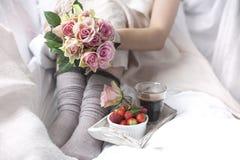 En bukett av rosa rosor i händerna av flickan på sängen, bär av jordgubbar och ett doftande morgonkaffe romantiker Royaltyfria Foton
