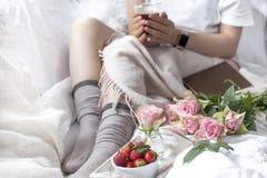 En bukett av rosa rosor i händerna av flickan på sängen, bär av jordgubbar och ett doftande morgonkaffe romantiker Arkivbilder