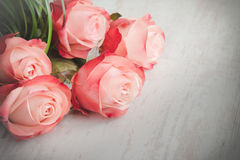 En bukett av rosor på en vit wood gammal bakgrund tappning för stil för illustrationlilja röd Arkivfoton