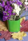 En bukett av torkade blommor i en grön vas står på stupade höstsidor av olika färger Allt detta på en torkdukegrå färgbakgrund Arkivbilder
