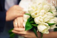 En bukett av vita tulpan i händerna av bruden och brudgummen A Royaltyfri Bild