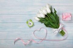 En bukett av vita tulpan och ett rosa band i form av en hjärta med en gåva och en ringklocka på hobsna royaltyfria bilder