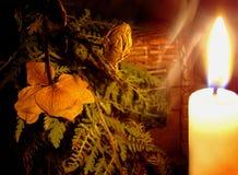 En bukett för häxa` s av torkade örter och blommor nära en brinnande stearinljus Royaltyfri Foto