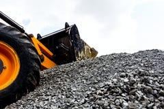 En bulldozer som upp väljer grus på jobsite. Arkivfoto