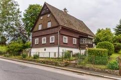 En bungalow som gjordes av trä med en brunn, underhöll trädgården runt om den royaltyfri fotografi