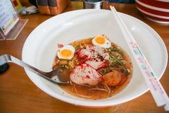 En bunke av den smakliga nudeln med ägg, finhackat griskött och rött griskött Arkivbilder