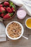 En bunke av hemlagad granola med yoghurt och nya jordgubbar på en träbakgrund Sund frukost med grönt te fotografering för bildbyråer