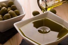 En bunke av olivolja med oliven i bakgrunden Royaltyfri Foto
