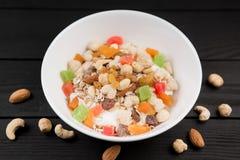 En bunke av sund frukostmysli med yoghurt och muttrar Royaltyfri Fotografi