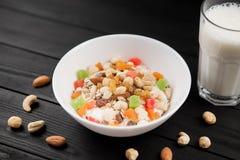 En bunke av sund frukostmysli med yoghurt och muttrar med exponeringsglas av mjölkar Arkivbilder