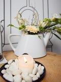 En bunke med en brinnande stearinljus som dekoreras med vita kiselstenar, glasflaska med vatten och kork och bredvid den en tekan royaltyfria foton