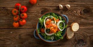 En bunke med nya sallad och tomater på en trätabell Arkivfoton