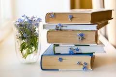 En bunt av böcker med små blåa blommor mellan sidor på den vita tabellen royaltyfria bilder