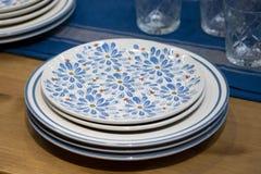 En bunt av blåa plattor med blommor på tabellen med en blå servett Table inställningen royaltyfria foton