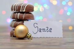 En bunt av choklad täckte kex och en guld- joller med en anmärkning för jultomten fotografering för bildbyråer
