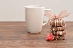 En bunt av choklad täckte kex som bands med ett rosa band Arkivfoton