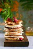 En bunt av frodiga punkcakes för frukost på en grå bakgrund Hög hög av läckra pannkakor med bär amerikansk kokkonst royaltyfri fotografi