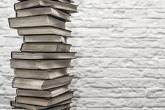 En bunt av gamla böcker på bakgrunden av tegelstenväggen Arkivbild