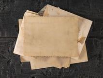 En bunt av gamla foto på en svart trätabell r ?vre sikt royaltyfri foto