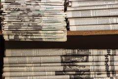 En bunt av gamla tidningar ligger på hyllan royaltyfria foton