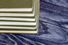 En bunt av gräsplan bokar på en trätabell begrepp av läs- hab Arkivbilder