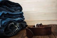 En bunt av jeans på en träbakgrund och ett bälte royaltyfri bild