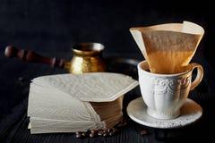 En bunt av kaffefilter från Kraft papper och vit kopp Makro arkivbild