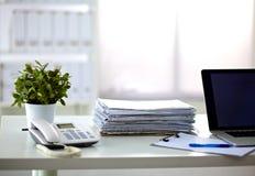 En bunt av legitimationshandlingar på skrivbordet med en dator royaltyfri fotografi
