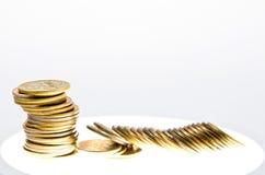 En bunt av mynt på en lysande tabell Arkivfoton