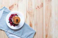 En bunt av pannkakor med blåbär och tranbär på en vit platta arkivbilder