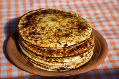 En bunt av vikta pannkakor Tjocka pannkakor från ugnen på en platta Royaltyfri Fotografi