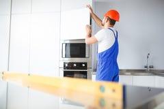 En byggmästare, i likformig, kontrollerar kvaliteten av installationen av dörren i kökskåpet arkivfoton