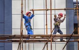 En byggmästare som går på ett material till byggnadsställning Arkivfoto