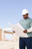 En byggmästare som rymmer en ritning Arkivfoton