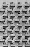 En byggnad med identiska balkonger och fönster med en skugga på Arkivfoto
