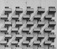 En byggnad med identiska balkonger och fönster med en skugga på Royaltyfri Fotografi