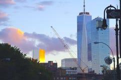 En byggnad reflekterar den guld- solnedgången som dras tillbaka av en strålningshimmel, NYC, NY Royaltyfri Bild