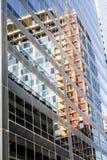 En byggnad reflekteras i ett annat byggande exponeringsglas Arkivbild