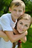 En cámara sonriente de la hermana adolescente y del pequeño hermano y de mirada feliz que abraza al aire libre Imagenes de archivo