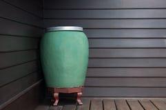En céramique fabriqué à la main de grand de l'eau d'art pot de vert sur le fond en bois de mur Photo stock