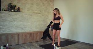 En caminar rubio atractivo de la señora del estudio aerobio espacioso grande recto mientras que saca la chaqueta de deporte y almacen de video