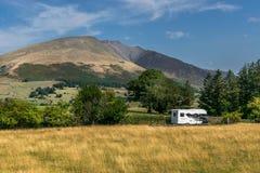 En campareskåpbil eller ett motoriskt hem bredvid ett berg royaltyfria bilder