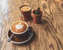 En cappuccino sitter på en trätabell bredvid något socker och en kaktus arkivbild