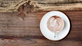 En cappuccinokopp med mjölkar skum och kanel Arkivbilder