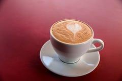 En cappuccinokopp på tabellen Arkivfoton