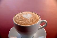 En cappuccinokopp på tabellen Royaltyfri Bild