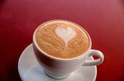 En cappuccinokopp på tabellen Royaltyfria Bilder