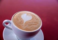 En cappuccinokopp på tabellen Royaltyfri Foto